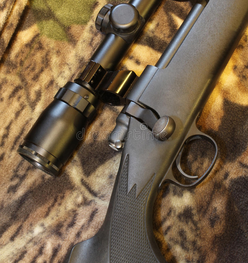 Rifle bolt and scope. Closeup of .30-06 rifle bolt and scope on camo background royalty free stock photography