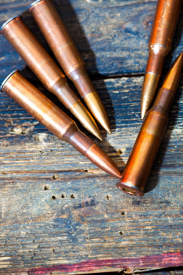 Rifle cartridges. On aged wooden surface royalty free stock image