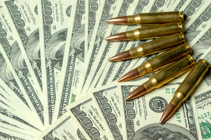 Rifle cartridges on dollars. Concept for crime, contract killing, paid assassin, terrorism, war, global arms trade. Weapons sale. Illegal hunting, poaching stock images