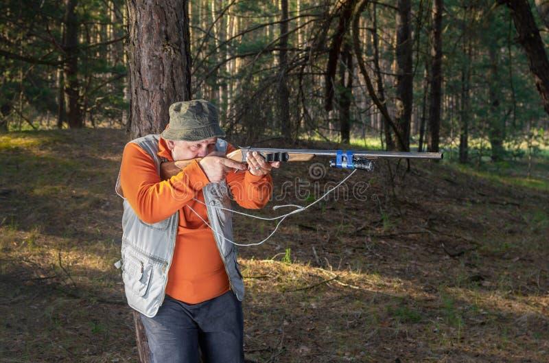 Rifle do alvo do caçador na floresta que inclina-se em um pinheiro imagem de stock royalty free