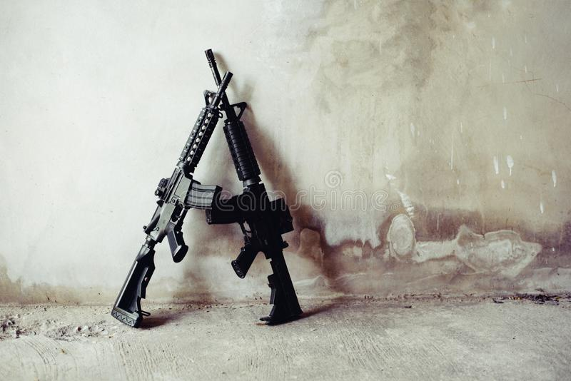 Rifle guns on grunge wall in abandoned house. Terrorist and Soldier concept. Robber and Police concept. War machine gun theme.  royalty free stock photography