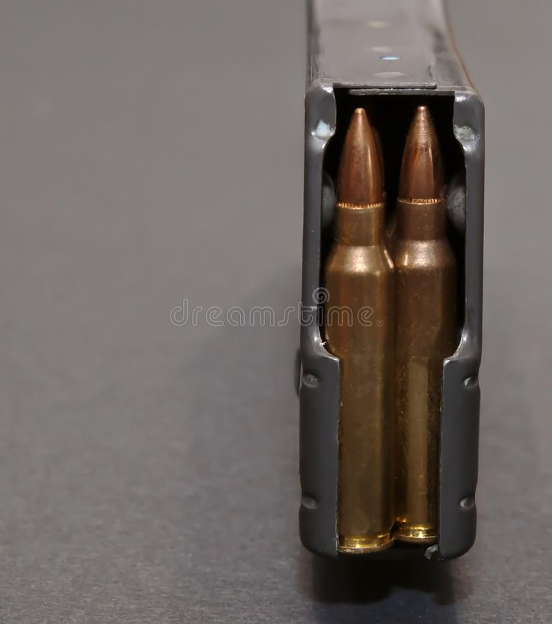 A rifle magazine loaded with .223 bullets. On a gray background royalty free stock photography