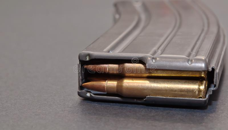 A rifle magazine loaded with .223 bullets. On a gray background royalty free stock photos