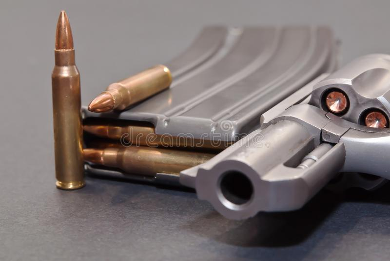 A rifle magazine loaded with .223 bullets and two extra ones next to a stainless 357 revolver. On a gray background stock image