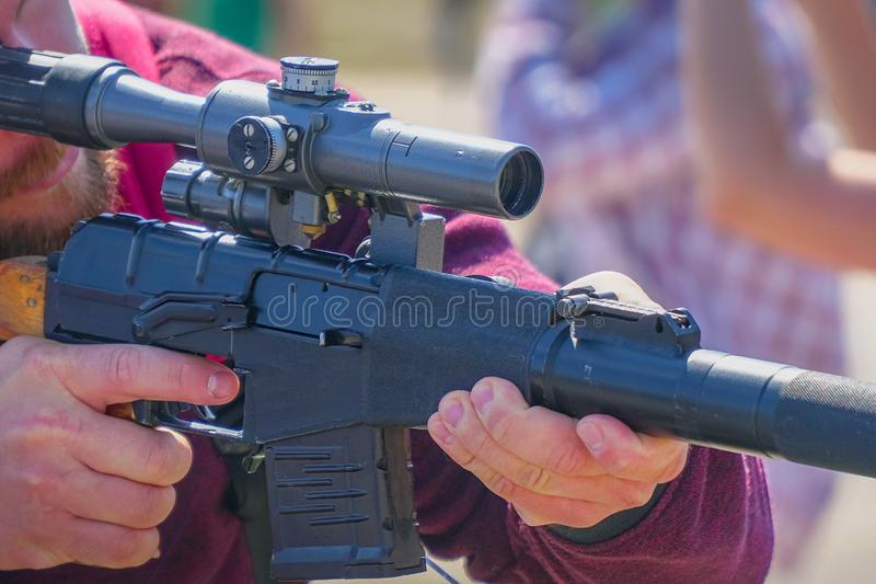 Rifle with an optical sight in hands of men stock photos
