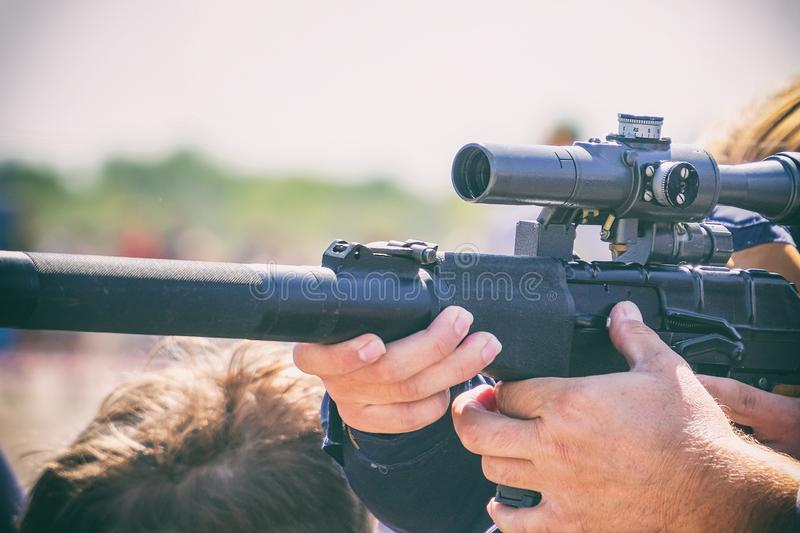 Rifle with an optical sight in hands of men stock image