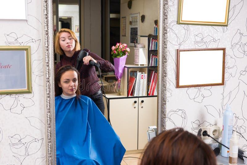 Riflessione dei capelli asciuganti col phon dello stilista del cliente immagini stock libere da diritti