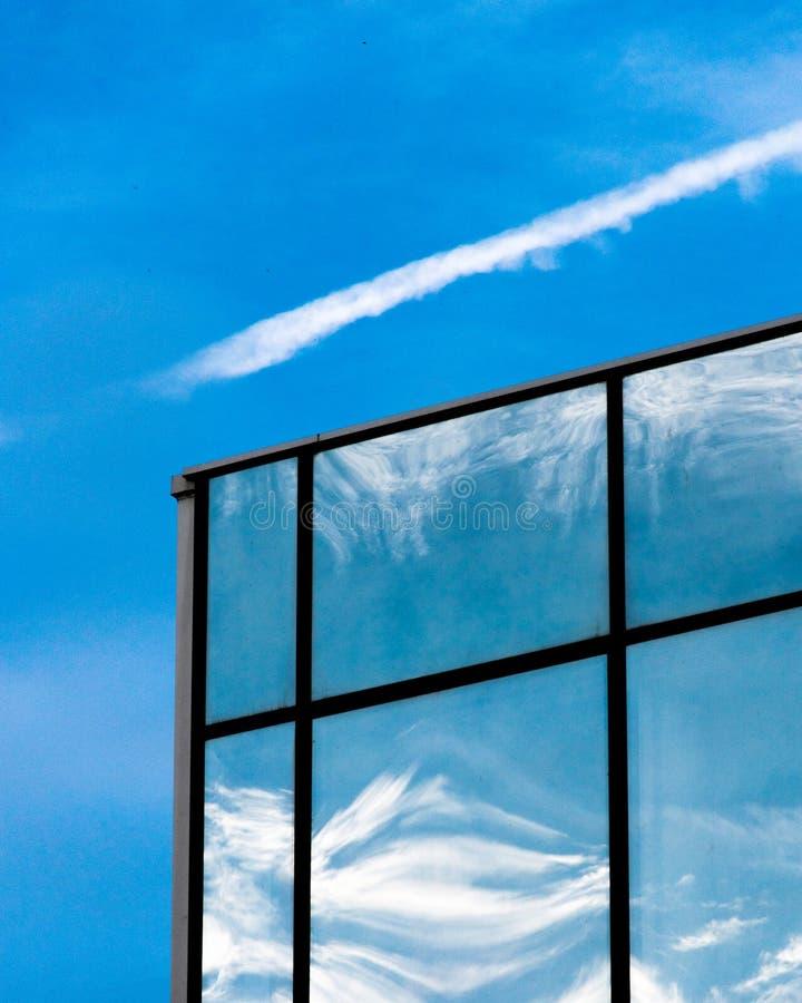 Riflessione del cielo blu sulle finestre della costruzione fotografia stock