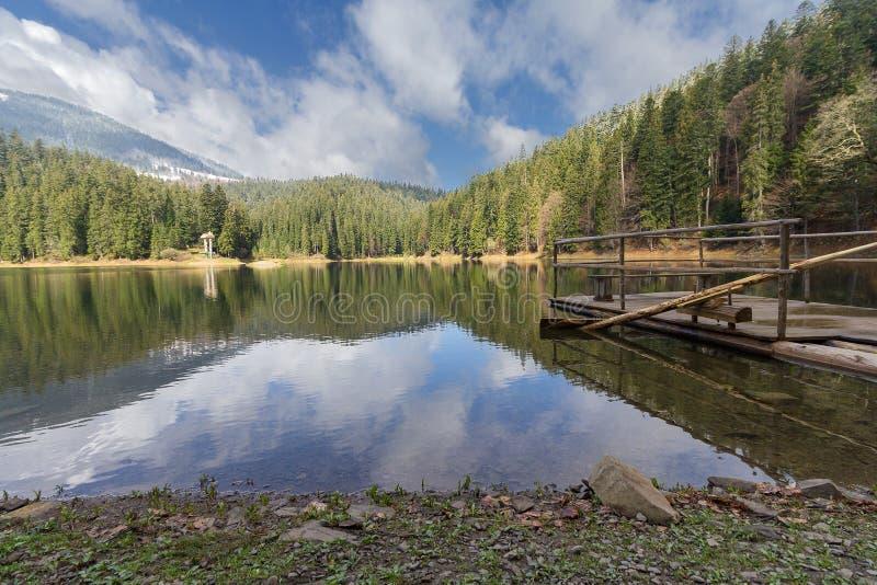 Riflessione del cielo e della zattera sul lago Synevir della montagna fotografia stock libera da diritti