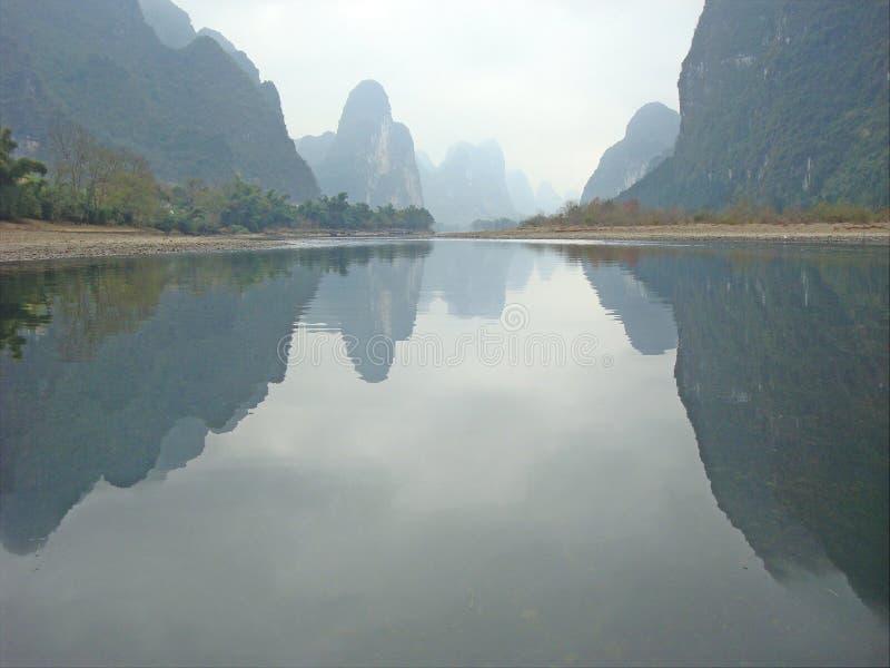 Riflessione del cielo e delle colline sulla superficie calma del fiume di Li in Yangshuo, Cina immagine stock libera da diritti
