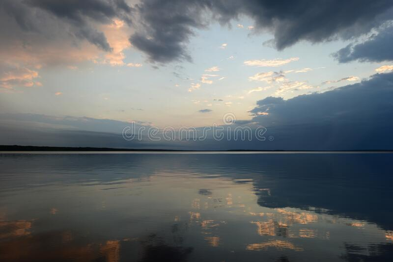 Riflessione del cielo nell'acqua del lago nella calma al tramonto fotografie stock