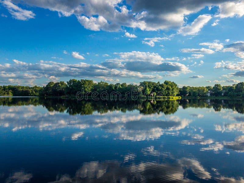 Riflessione del cielo nuvoloso nell'acqua di poco lago fotografia stock