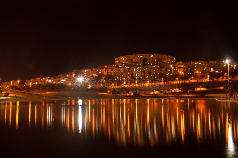 Riflessione della città di notte nel lago Modiin Israele fotografia stock