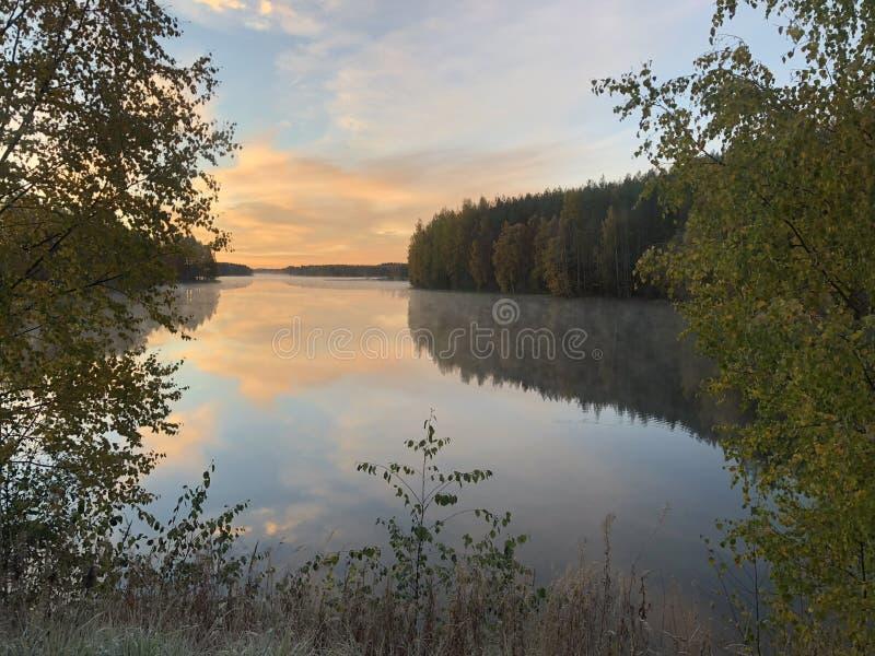 Riflessione della riva nell'acqua e nelle nuvole ardenti luminose fotografia stock