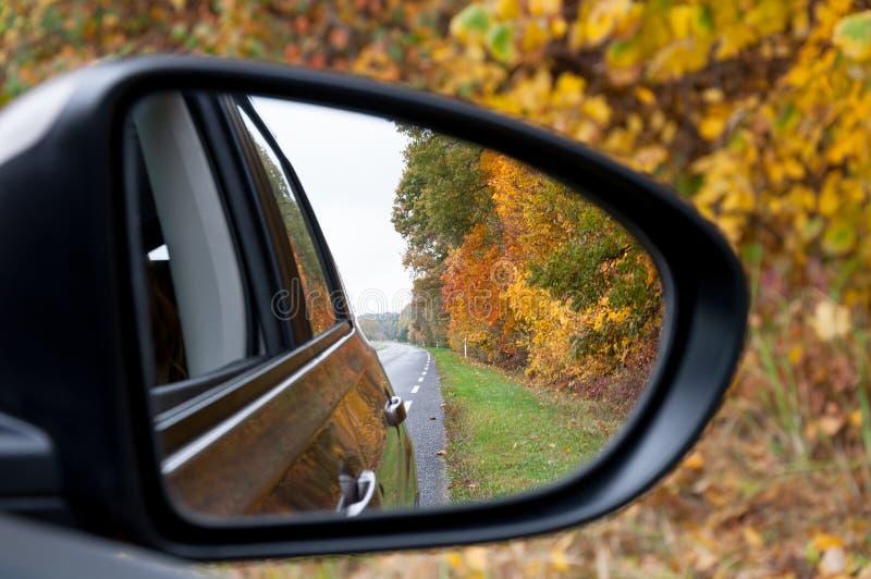 Riflessione della strada di autunno dello specchio di automobile fotografie stock