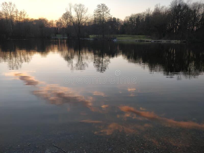 Riflessione delle nuvole in acqua ad alba o al tramonto fotografie stock libere da diritti