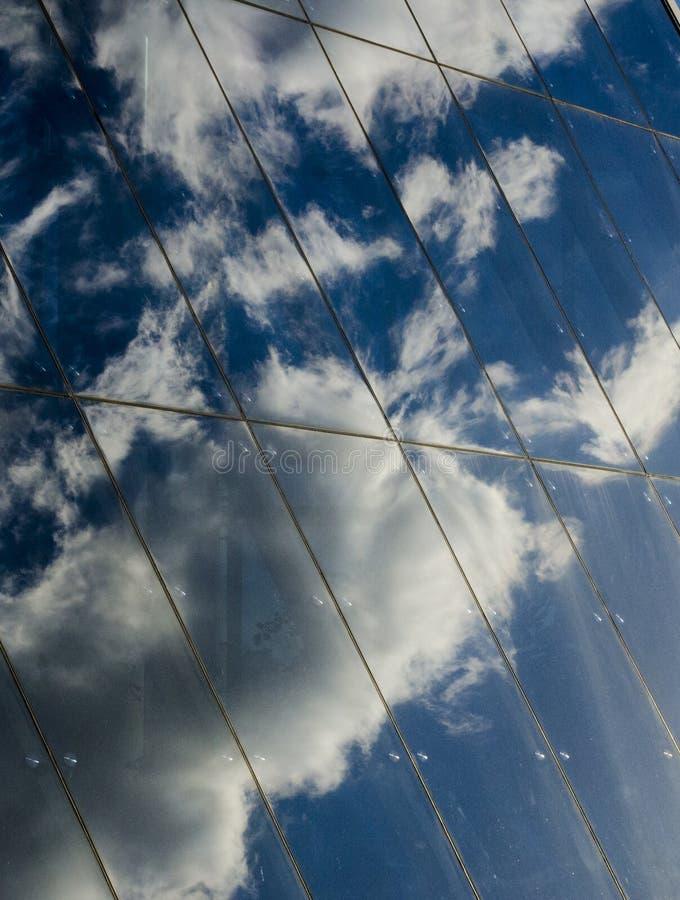 Riflessione delle nuvole e del cielo blu nella parete di vetro di un moderno immagine stock libera da diritti