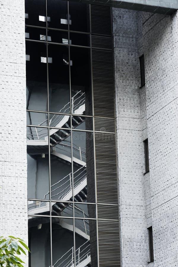 Riflessione delle scale di emergenza nel vetro di una costruzione moderna con le pareti grige del cemento fotografia stock