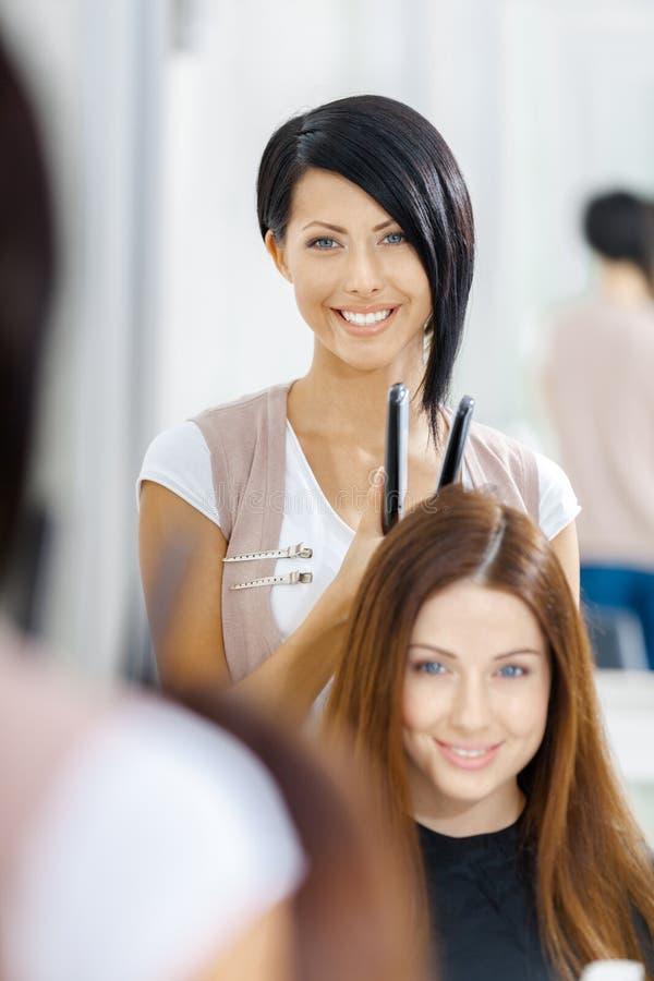 Riflessione dello stilista di capelli che fa stile di capelli per la donna immagini stock