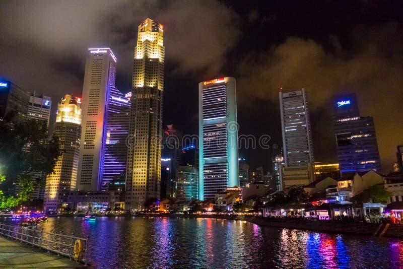 Riflessione di Singapore delle costruzioni e del fiume moderni del grattacielo alla notte fotografie stock libere da diritti