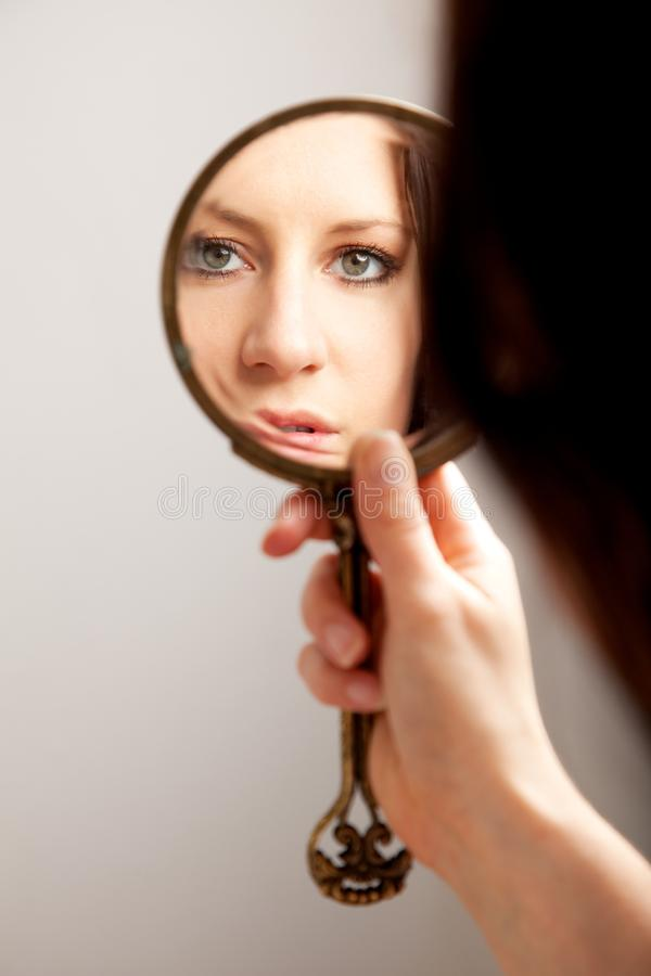 Riflessione di specchio del primo piano del fronte della donna fotografia stock