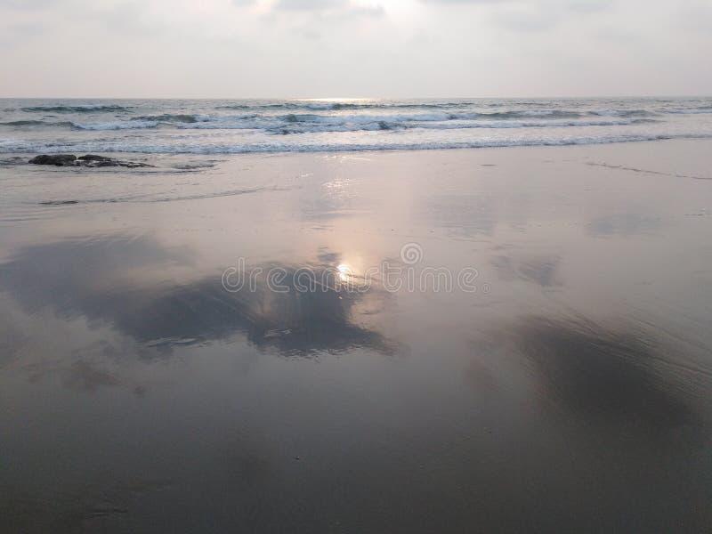 Riflessione di Sun nel mare entro la sera Goa, India immagini stock libere da diritti