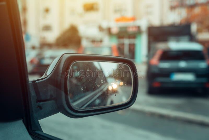 Riflessione di traffico cittadino in specchio del lato dell'automobile immagini stock