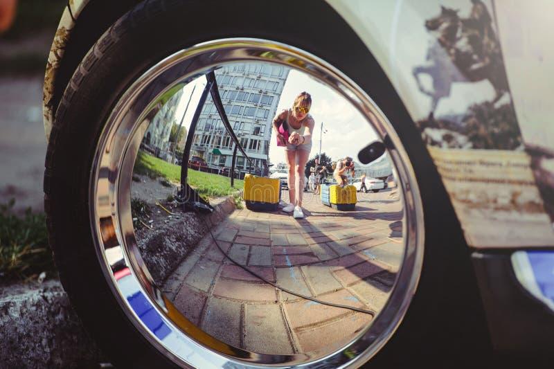Riflessione di una donna in una ruota di automobile del cromo immagini stock