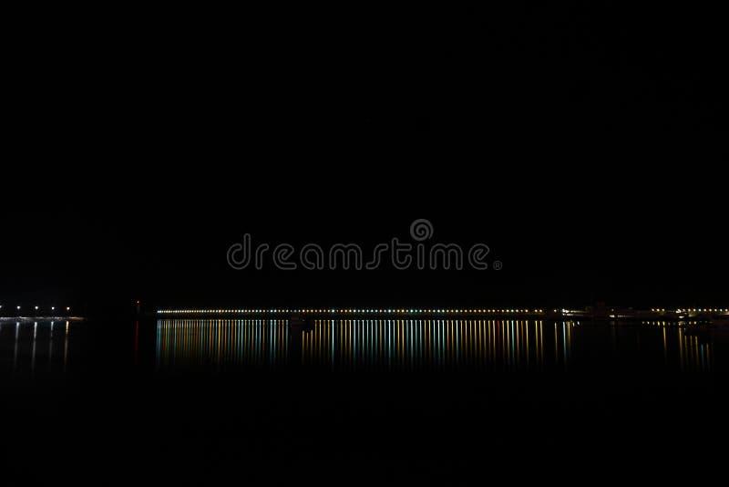 Riflessione leggera variopinta nell'acqua scura di notte Suo un'ombra luminosa lunga a creare un bello momento immagine stock