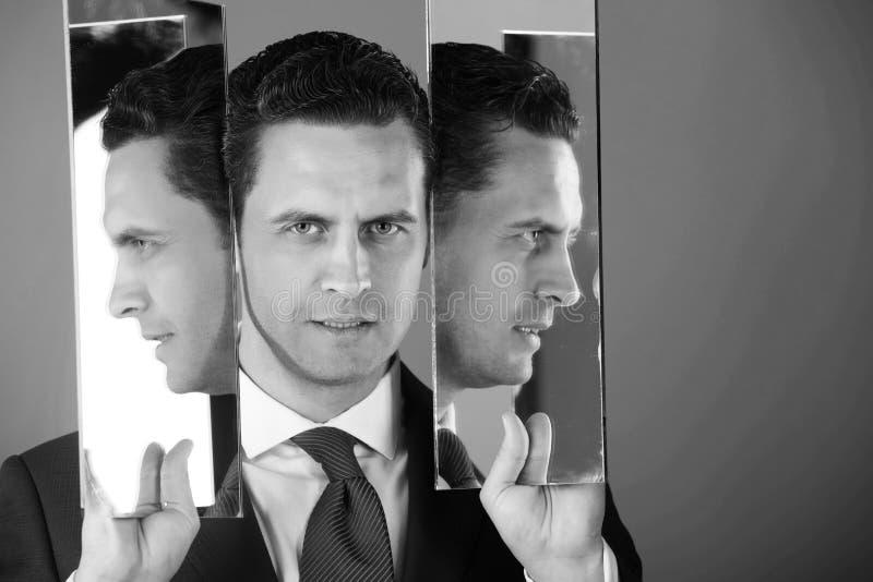 Riflessione sul fronte dell'uomo e profili in due specchi immagini stock libere da diritti