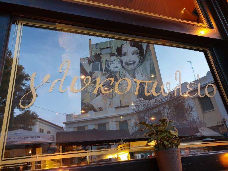 Riflessione in una finestra del negozio di pasticceria dei graffiti su una facciata di costruzione nel quadrato degli eroi nella  fotografia stock