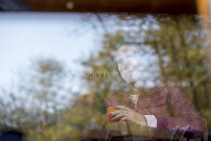 Riflessioni degli alberi su vetro con una donna dietro immagine stock libera da diritti
