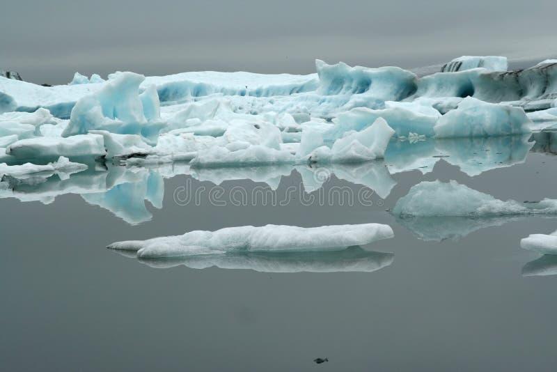 Riflessioni dei icerbergs blu e bianchi di cristallo in acqua scura nera in ghiacciaio luminoso triste tenue di Jökulsárlón Jokul fotografia stock libera da diritti