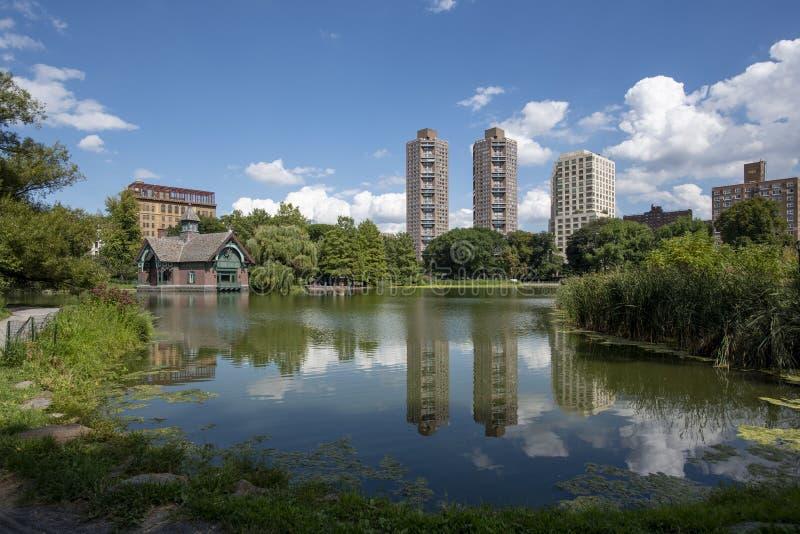 Riflessioni delle nuvole e delle costruzioni al Harlem Meer in NYC fotografia stock
