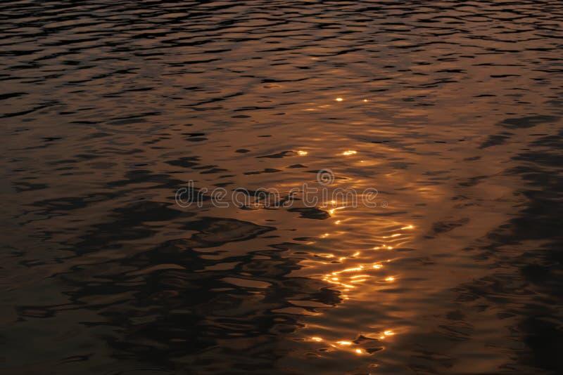 Riflessioni in un'acqua nei colori dorati immagine stock
