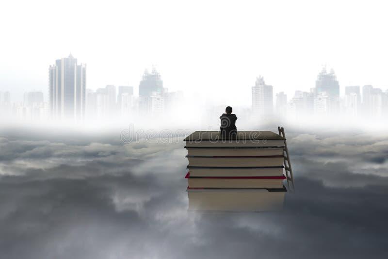 Riflettere uomo che si siede sulla pila di libri con il cloudscap di paesaggio urbano fotografia stock libera da diritti