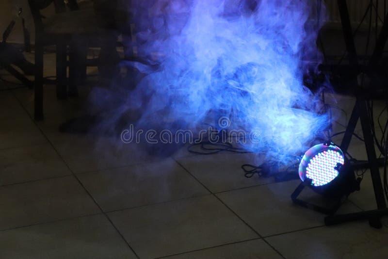 Riflettore blu del LED sul pavimento con fumo nella stanza scura vicino ai cavi ed alle colonne con lo spazio della copia immagini stock libere da diritti
