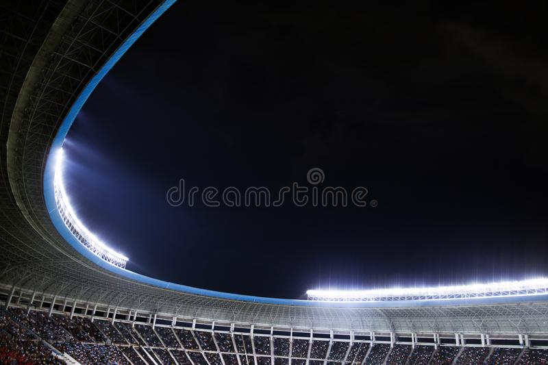 Riflettori e proiettori ad uno stadio alla notte immagine stock