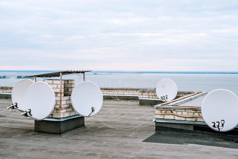 Riflettori parabolici, antenne satellitari sopra la costruzione nell'area urbana vicino al fiume immagine stock