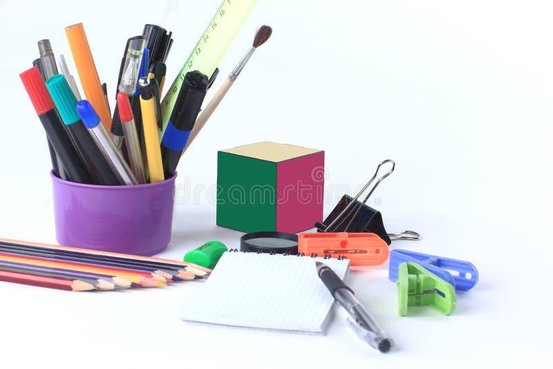 Rifornimenti del cubo e di scuola del ` s di Rubik Isolato su priorità bassa bianca fotografie stock libere da diritti