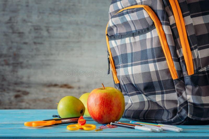 Rifornimenti dello zaino, della mela e di scuola su fondo di legno immagine stock libera da diritti