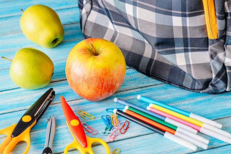 Rifornimenti dello zaino, della mela e di scuola su fondo di legno fotografie stock
