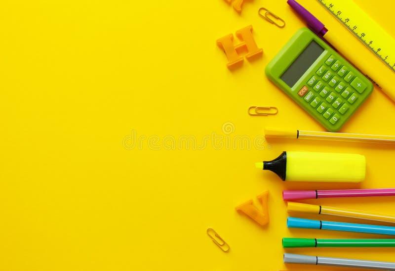 Rifornimenti di banco su priorit? bassa gialla Di nuovo al concetto della scuola con spazio per testo Vista superiore Copi lo spa immagine stock