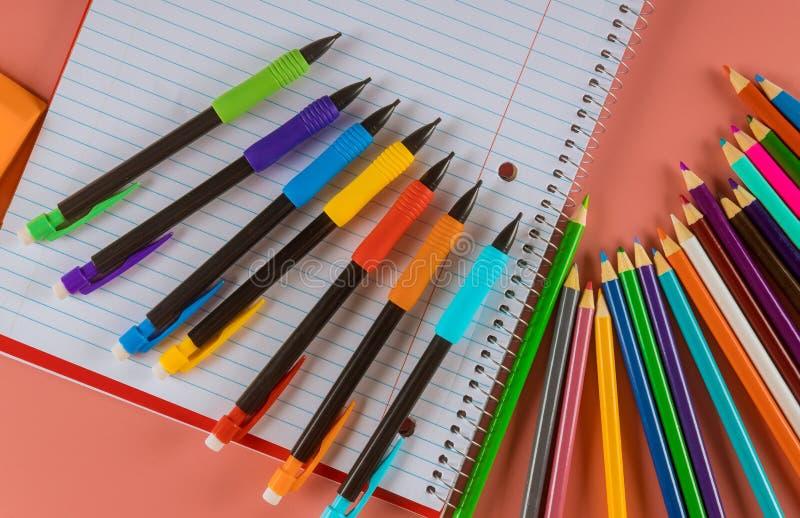 Rifornimenti di scuola con taccuini e matite di colori fotografia stock
