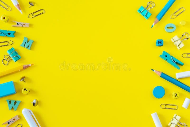 Rifornimenti di scuola multicolori su fondo giallo con lo spazio della copia fotografie stock libere da diritti