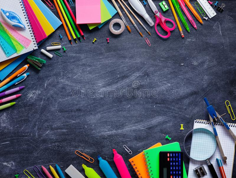Rifornimenti di scuola nel telaio sulla lavagna fotografia stock
