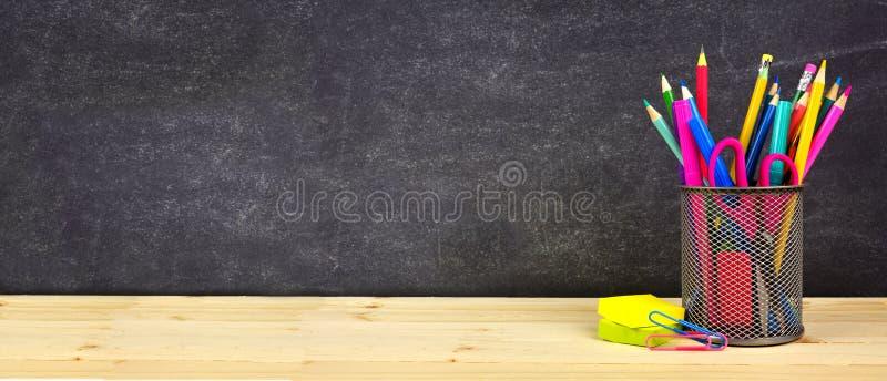Rifornimenti di scuola su uno scrittorio di legno con il fondo della lavagna Di nuovo al banco Copi lo spazio bandiera fotografia stock