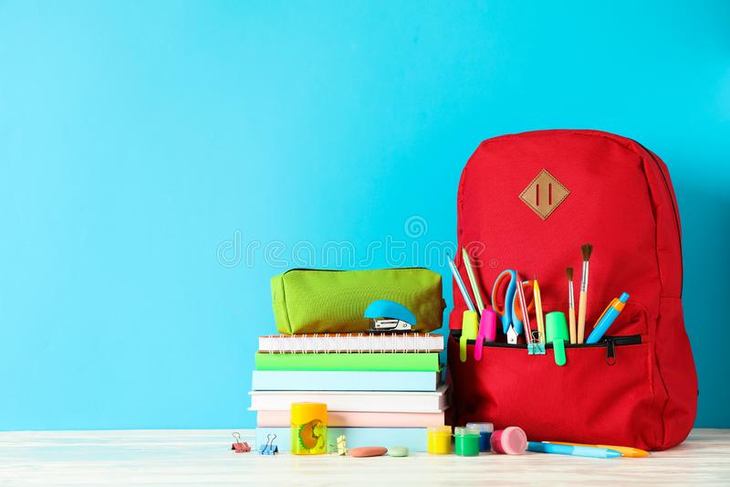 Rifornimenti di scuola sulla tavola di legno contro il fondo di colore fotografia stock libera da diritti