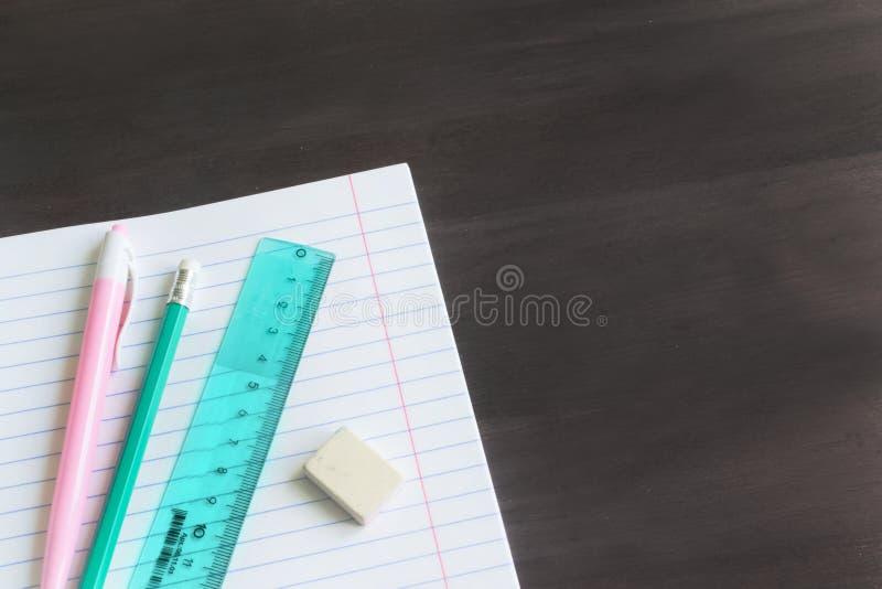 Rifornimenti ed accessori di scuola sul fondo della lavagna Concetto di nuovo alla scuola fotografia stock
