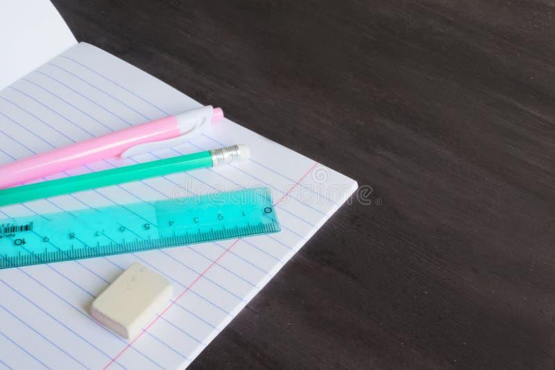 Rifornimenti ed accessori di scuola sul fondo della lavagna Concetto di nuovo alla scuola immagine stock